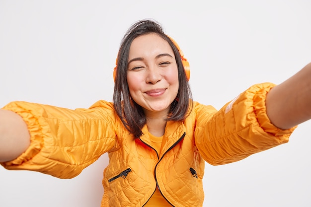 Sincere positive asian woman stretches arm forward makes selfie being in good mood listens audio track uses stereo wireless headphones dressed in jacket isolated over white  wall