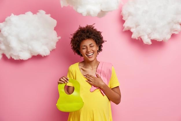 誠実な前向きな妊産婦は笑ってベビー用品を購入し、ゴム製のよだれかけを持ち、肩の幼児のボディスーツは本当の宝物の楽しい期待として新しい人生を高く評価しています。すぐに私は幸せなお母さんになります