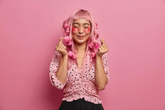 긴 분홍색 머리카락을 가진 성실한 긍정적 인 여성, 롤러를 바르고, 곱슬 머리를 만들고, 한국 심장 기호를 보여주고, 붓기를 줄이기 위해 장밋빛 콜라겐 패치를 착용합니다.