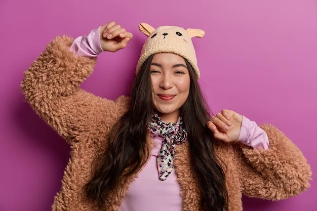 長い髪の誠実なきれいな女性は、腕を空中に上げ続け、カメラで陽気に見え、健康な肌を持ち、帽子と冬のコートを着て、薄紫色の空間で隔離されています