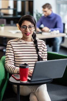 Sincere smile. delighted girl sitting in cafe while working online on distance