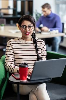 Искренняя улыбка. довольная девушка сидит в кафе во время работы онлайн на расстоянии