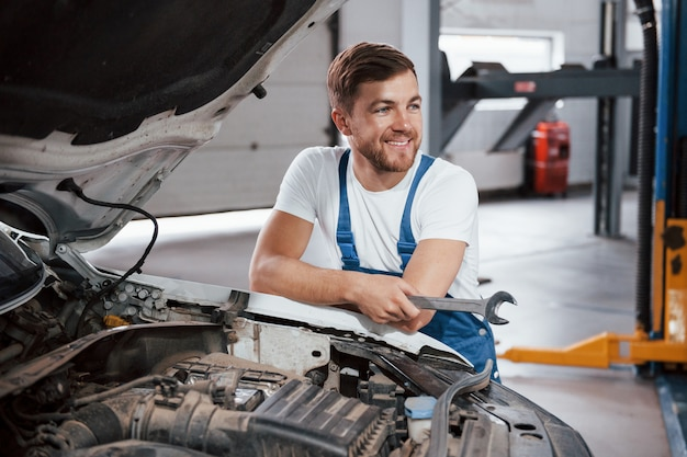 Sincere smile. employee in the blue colored uniform works in the automobile salon