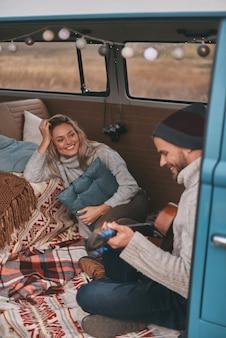 진지한 미소. 파란색 복고풍 스타일의 미니 밴에 앉아있는 동안 그의 아름다운 여자 친구를 위해 기타를 연주하는 잘 생긴 젊은 남자의 상위 뷰