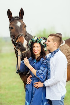 Sincere smile of womanfriend in festive clothes that stands next to the guy and holds the horse behind the bridle