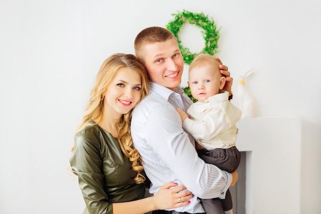 暖炉と緑の花輪を背景に幼い息子を手に持っている両親の心からの笑顔