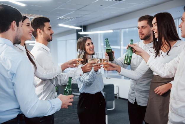 Искренние улыбки стоя и выбивая бутылки и бокалы. в офисе. молодые люди празднуют свой успех