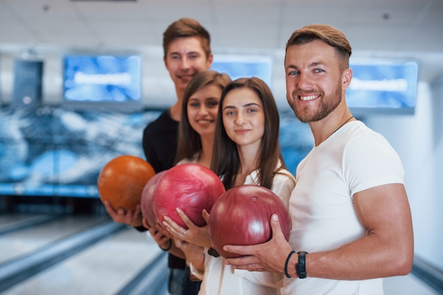 Sorrisi sinceri. i giovani amici allegri si divertono al bowling durante i fine settimana
