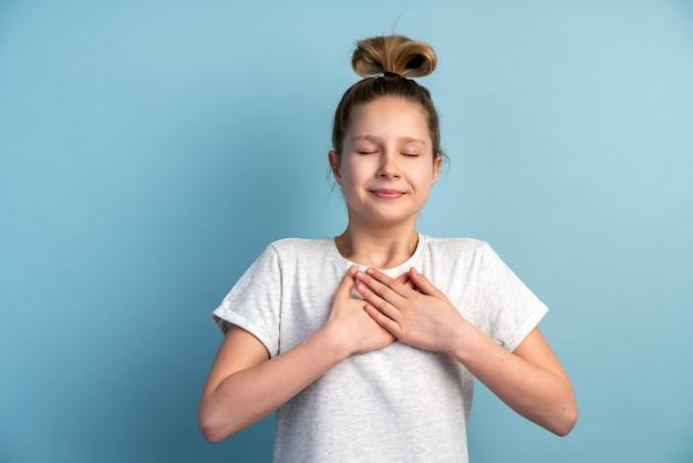誠実な、笑顔の十代の少女は心、魂からのジェスチャーを示しています