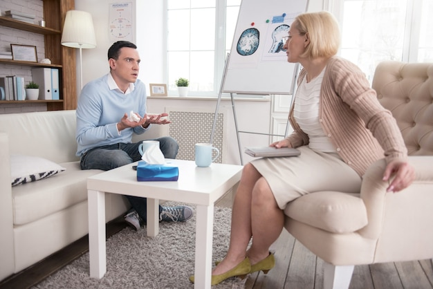 Sincere tears. anxious stressful man communicating with senior psychologist while crying