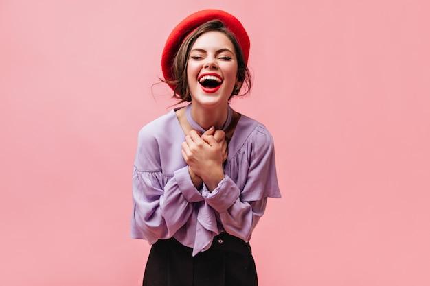 붉은 입술을 가진 성실한 여자는 분홍색 배경에 웃고있다. 주름과 블라우스에 갈색 머리의 총입니다.