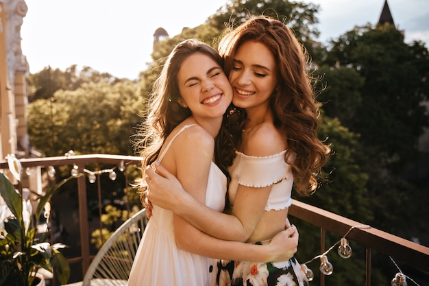 Donne sincere che si abbracciano sul balcone