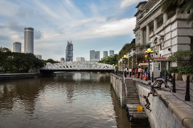 Сингапур - 9 декабря 2014: вид на скульптурную композицию скульптора «первое поколение» чонг фа чеонг на реке сингапур, район риверсайд. рядом с отелем фуллертон.