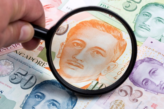 Singapore dollar in a magnifying glass a business background