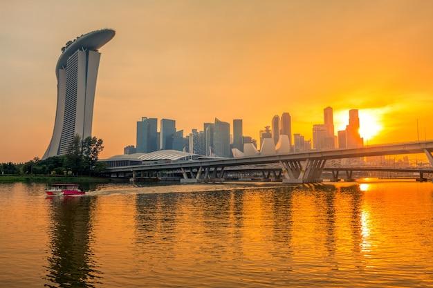 サンドホテル、高層ビル、2つの橋があるシンガポールのダウンタウン。黄金の夕日と美しい夜の照明