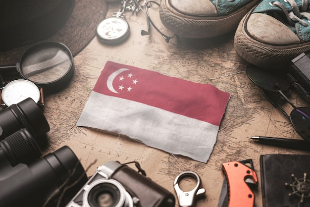 古いビンテージ地図上の旅行者のアクセサリー間のシンガポール国旗。観光地のコンセプト。