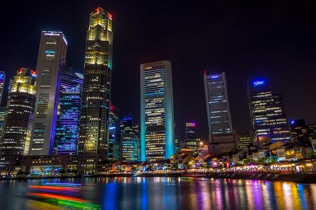 Сингапур. набережная с кафе и небоскребами. прогулочные катера. ночь