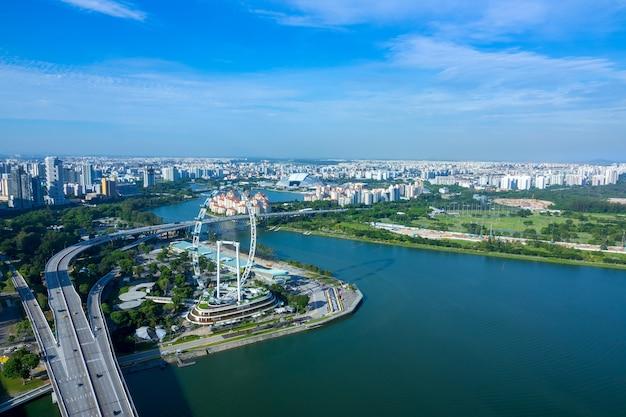 シンガポール。晴れた日。住宅地、観覧車、高速道路のパノラマ。航空写真