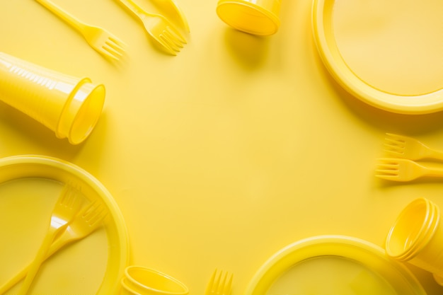 Singe use picnic utensils for recycling on yellow.