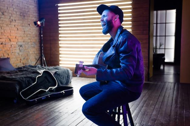 ネオンライトのあるステージで歌う歌手とギター奏者。彼はロッカーで、革のバイカージャケットまたは黒のキャップとジーンズが付いた非対称のジップジャケットを着ています。