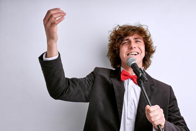 白い背景で隔離のポーズのスーツの歌手の男。人々のライフスタイルの概念。男性がマイクで歌を歌う