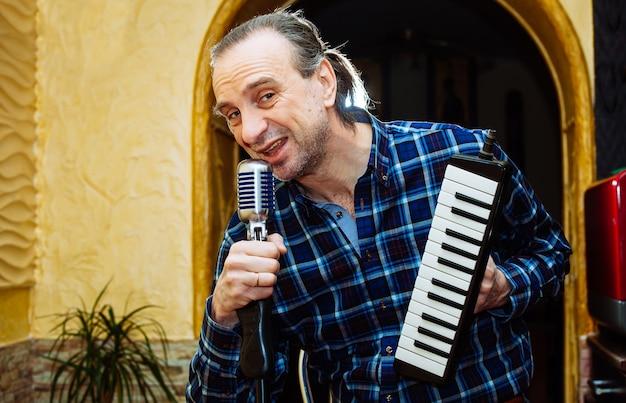 Певец со старомодным микрофоном и фортепиано