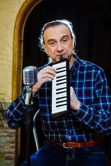 Певец мужчина со старомодным микрофоном и фортепиано