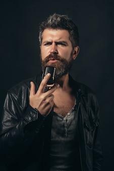 Певица, музыка, шоу-бизнес, люди, технологии, концепция голоса - бородатый певец в элегантной черной куртке с микрофоном на сцене. супер рок-звезда, вокалист в темноте. рок-звезда мужского пола поет на концерте.