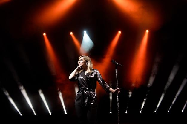 Певица на сцене в клубе. яркое сценическое освещение.