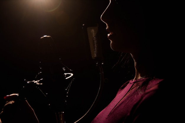Singer recording a song in music studio.