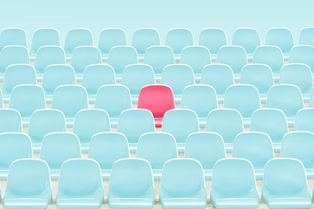 Singer red seat in the middle of light blue chair in stadium .