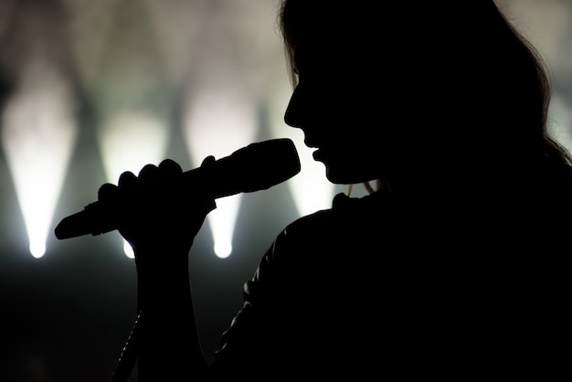 Singer in silhouette. close up image of live singer on stage
