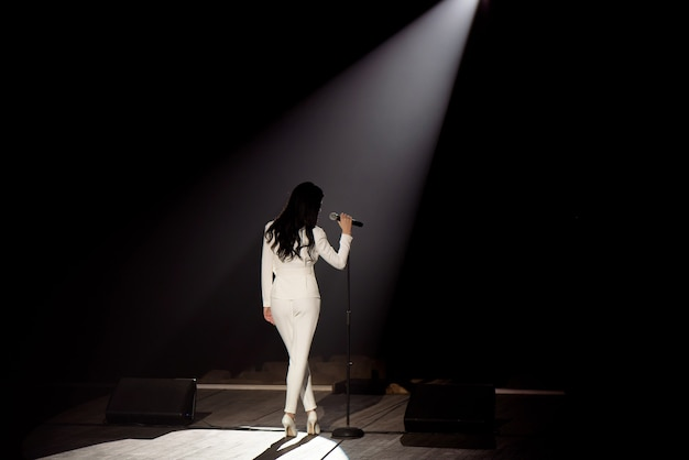 Singer on stage in a beam of white light.