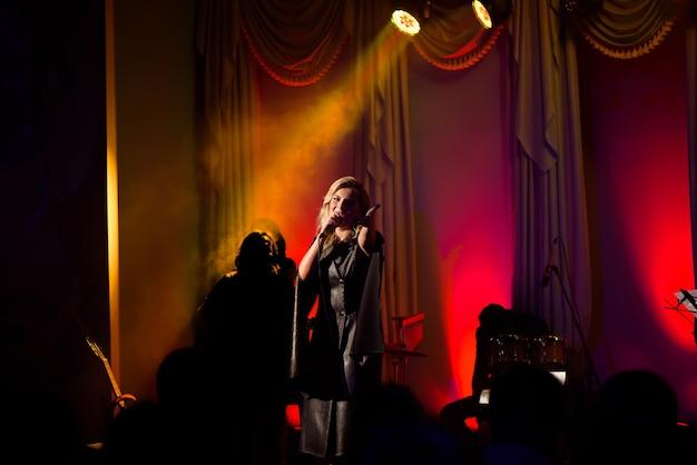 Певица со своим оркестром выступает на сцене. концерт. вид из зрительного зала.