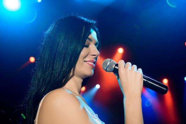Певица с микрофоном на фоне красочной светлой сцены.