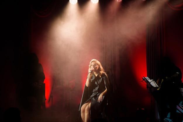 Певица с микрофоном на сцене в сценическом освещении.