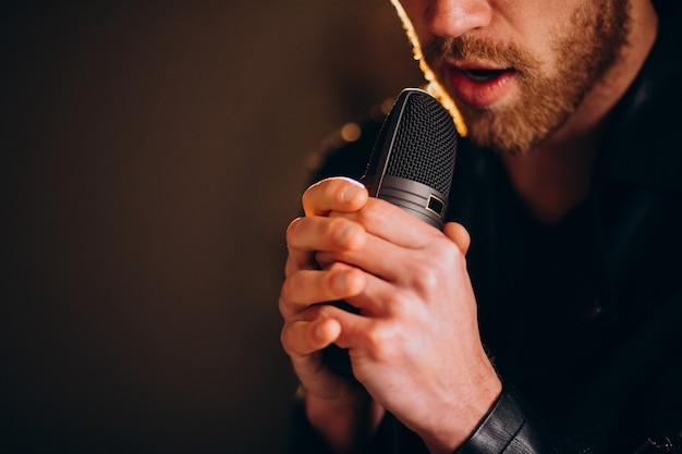 スタジオでマイクを使って歌う歌手