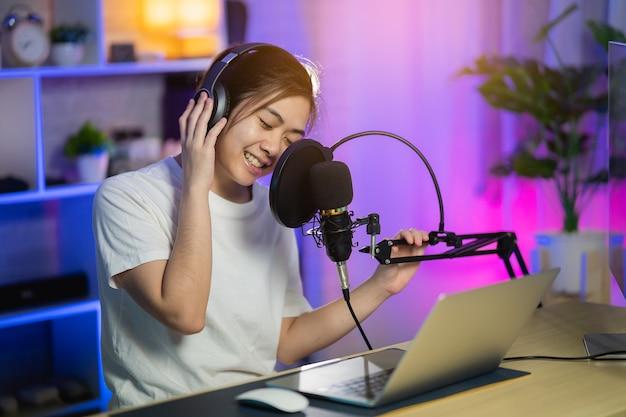 ホームレコーディングスタジオで新曲を録音するヘッドフォンで歌う歌手の女性