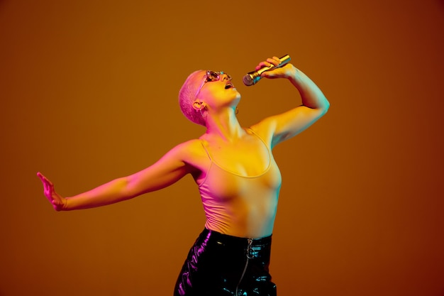 Cantante. giovane donna caucasica su marrone alla luce al neon. bellissimo modello femminile con microfono, altoparlante.