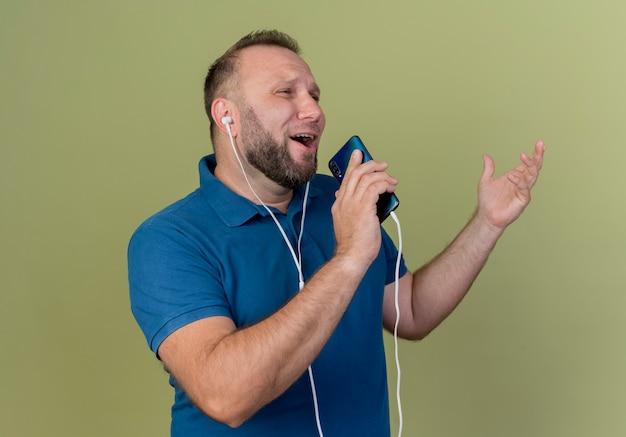 Singing adult slavic man wearing earphones looking straight keeping hand in air using mobile phone as microphone