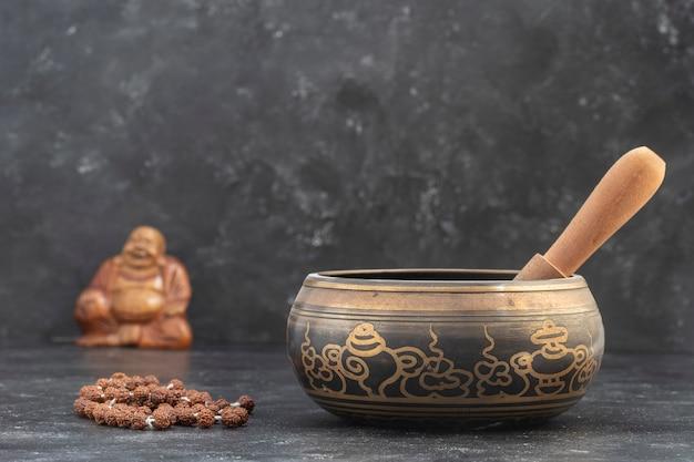 회색 배경에 나무 막대기와 티베트 구슬로 된 묵주가 있는 노래하는 그릇. 명상, 요가, 자기 개발 및 소리 치료 개념. 클로즈업, 복사 공간
