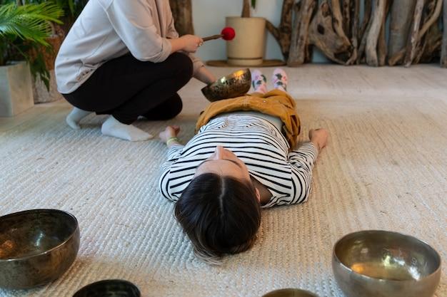 집에서 노래하는 그릇 마사지 : 두 명의 여성이 명상 개념을 위해 전통적인 청동 그릇의 진동과 음악과 티베트 대체 의학의 징을 사용하여 함께 티벳 소리 치료를 연습합니다.