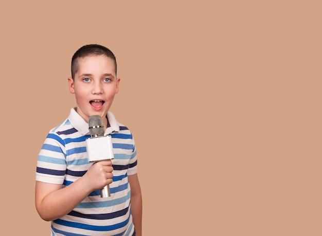 노래하는 아이는 그의 손에 마이크를 보유하고 있습니다. 그의 노래를 녹음하는 소년