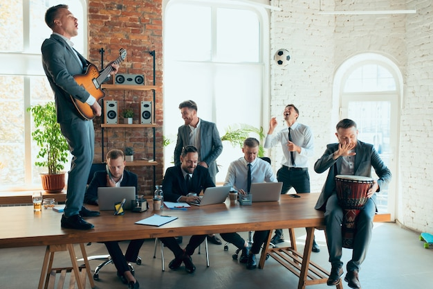Пение, музыкальный концерт, танцы. счастливые беззаботные коллеги веселятся в офисе, в то время как их коллеги усердно и сосредоточенно работают. понятие о развлечениях, отдыхе, профессиональном занятии.