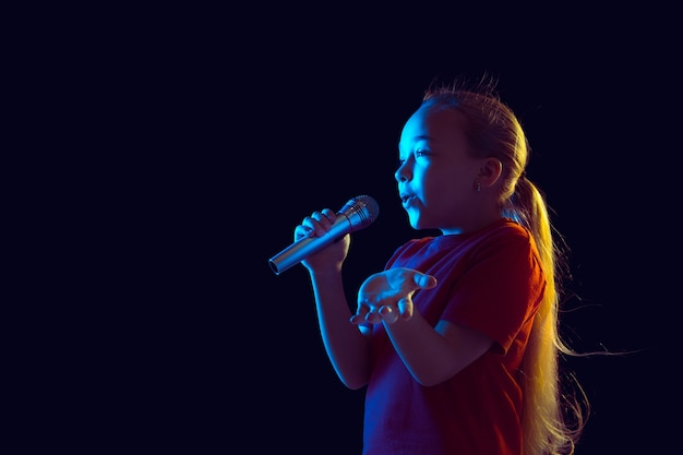 Cantando felice. ritratto della ragazza caucasica sulla parete scura alla luce al neon. bellissimo modello femminile con altoparlante. concetto di emozioni umane, espressione facciale, vendite, pubblicità, hobby, sogno, musica.