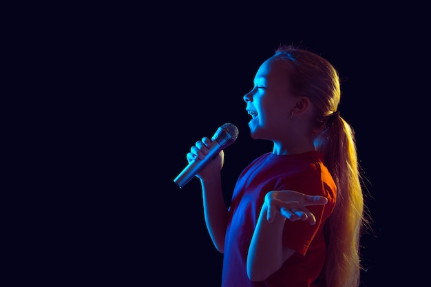 Пение счастливое. портрет кавказской девушки на темном фоне студии в неоновом свете. красивая женская модель с динамиком. понятие человеческих эмоций, выражения лица, продаж, рекламы, хобби, мечты, музыки.