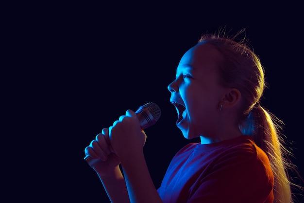 幸せに歌う。ネオンの光の暗いスタジオの背景に白人の女の子の肖像画。スピーカー付きの美しい女性モデル。