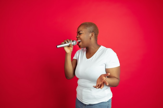 Singing inspired. african-american young woman's portrait on red