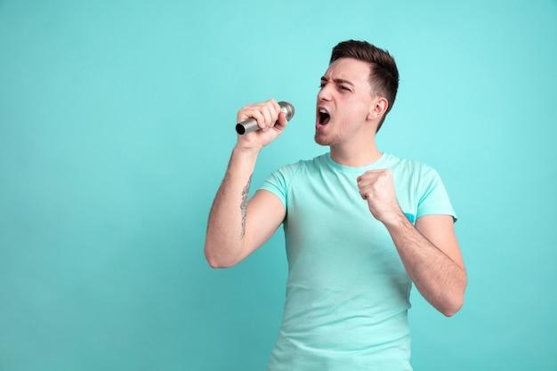 星のように歌う。青い壁に分離された白人の若い男の肖像画。パステルカラーのカジュアルスタイルの美しい男性モデル。人間の感情、顔の表情の概念