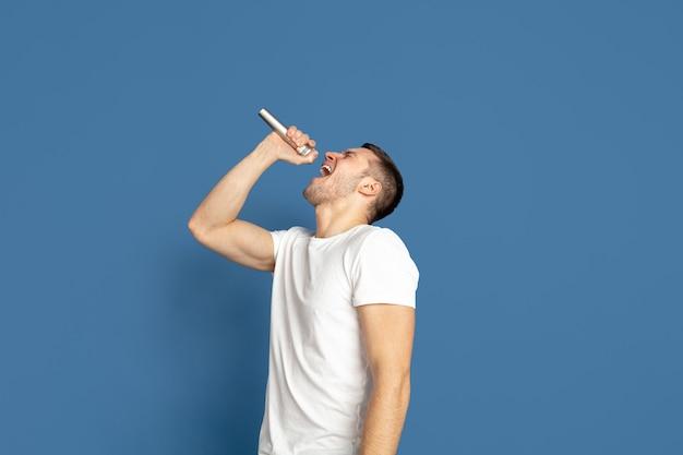Cantando come celebrità, star. ritratto di giovane uomo caucasico su sfondo blu.